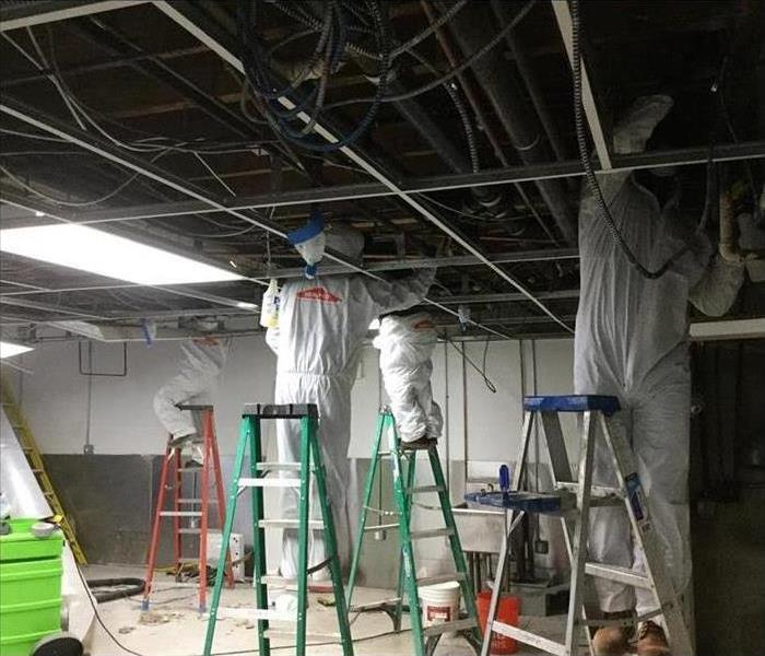 Technicians wearing protective gear, working on ceiling