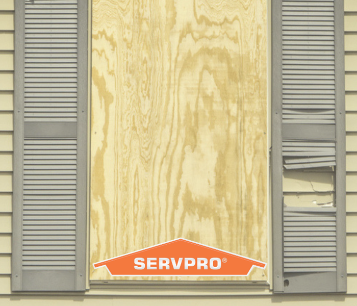 a board placed over a window opening on the exterior of a home